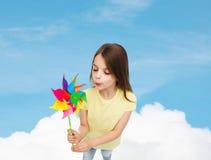 Niño sonriente con el juguete colorido del molino de viento Fotografía de archivo