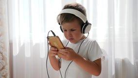 Niño sonriente con el móvil en el brazo que disfruta de música en auriculares y que baila en sitio almacen de metraje de vídeo