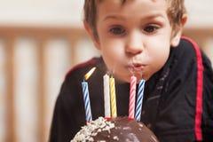 Niño sonriente con la vela de la torta de cumpleaños Fotos de archivo
