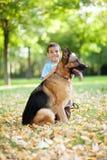 Niño sonriente con un pastor alemán Dog en el parque foto de archivo