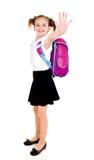 Niño sonriente de la colegiala con decir de la mochila adiós aislado foto de archivo