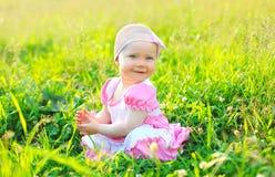 Niño sonriente de la foto soleada que se sienta en la hierba en verano Foto de archivo libre de regalías