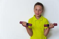 Niño sonriente del tween que hace ejercicio del bíceps Fotografía de archivo libre de regalías