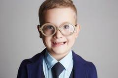 Niño sonriente divertido en vidrios y siut Foto de archivo