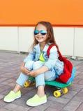 Niño sonriente elegante de la niña con el monopatín que se divierte Fotos de archivo libres de regalías