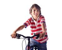 Niño sonriente en fondo del blanco de la bicicleta Foto de archivo libre de regalías