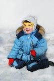 Niño sonriente en la nieve Fotos de archivo