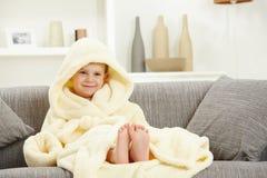 Niño sonriente en pies desnudos del sofá de la albornoz en casa Imagen de archivo libre de regalías