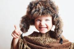 Niño sonriente en sombrero de piel Embroma estilo casual del invierno pequeño muchacho divertido de la moda Emoción de los niños Imagenes de archivo