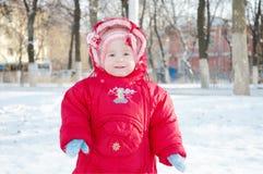 Niño sonriente en una calle nevosa imagenes de archivo