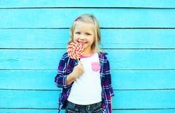 Niño sonriente feliz con la piruleta dulce del caramelo que se divierte Foto de archivo libre de regalías