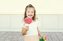 Niño sonriente feliz con la piruleta dulce del caramelo que se divierte en ciudad Fotos de archivo libres de regalías