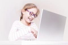 Niño sonriente feliz de la muchacha del niño usando el ordenador portátil imágenes de archivo libres de regalías