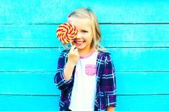 niño sonriente feliz de la niña del retrato con un palillo de la piruleta Imagen de archivo
