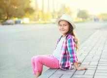 Niño sonriente feliz de la niña que lleva una camisa y un sombrero rosados a cuadros Foto de archivo libre de regalías
