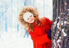 Niño sonriente feliz del retrato del invierno pequeño que juega cerca de árbol foto de archivo libre de regalías