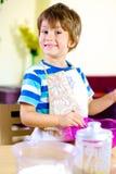 Niño sonriente feliz que cocina en casa imagen de archivo libre de regalías