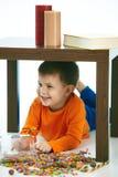 Niño sonriente feliz que miente debajo de la tabla con los dulces imagen de archivo