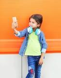 Niño sonriente feliz que toma el autorretrato de la imagen en smartphone en ciudad Imagen de archivo libre de regalías