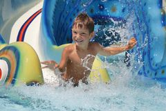 Niño sonriente joven que se divierte en aquapark Imágenes de archivo libres de regalías