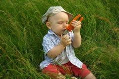 Niño sonriente maravilloso con alicates anaranjados Imagen de archivo libre de regalías