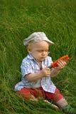 Niño sonriente maravilloso con alicates anaranjados Fotografía de archivo libre de regalías
