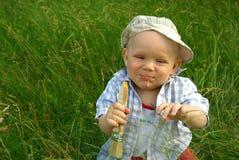 Niño sonriente maravilloso con un cepillo para pintar Imagenes de archivo