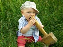 Niño sonriente maravilloso con un martillo de madera Imagen de archivo