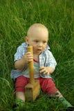 Niño sonriente maravilloso con un martillo de madera Foto de archivo