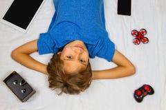 Niño sonriente que miente en la cama blanca y la mirada de la cámara Teléfono móvil, tableta, abejón y vidrios de VR alrededor de Imagenes de archivo