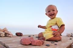 Niño sonriente que se sienta en la tabla Imagen de archivo libre de regalías