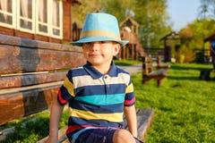 Niño sonriente que se sienta en un banco de parque con el prado verde en fondo Foto de archivo