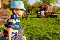 Niño sonriente que se sienta en un banco de parque con el prado verde en fondo Fotos de archivo libres de regalías