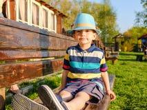 Niño sonriente que se sienta en un banco de parque con el prado verde en fondo Foto de archivo libre de regalías