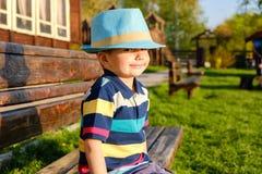 Niño sonriente que se sienta en un banco de parque con el prado verde en fondo Imagenes de archivo