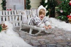 Niño sonriente sledding en la yarda del invierno de la nieve Imagen de archivo libre de regalías