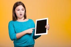 Niño sorprendente con una tableta digital en las manos poiting en ella Imagen de archivo
