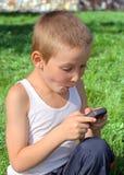 Niño sorprendido con el teléfono móvil Imagen de archivo