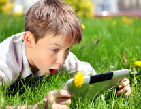 Niño sorprendido con la tableta Imagenes de archivo