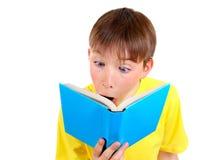 Niño sorprendido con un libro Fotos de archivo libres de regalías