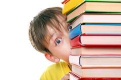 Niño sorprendido detrás de los libros Imagenes de archivo