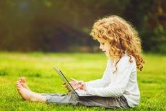 Niño sorprendido feliz con el ordenador portátil que se sienta en la hierba Fotos de archivo