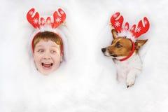 Niño sorprendido y un perro en una mentira del traje del reno en la nieve Fotografía de archivo