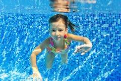 Niño subacuático sonriente feliz en piscina Fotografía de archivo