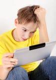 Niño subrayado con la tableta Imágenes de archivo libres de regalías