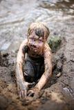 Niño sucio de Little Boy que juega en fango mientras que nada en el Rive imagen de archivo libre de regalías