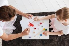 Niño talentoso vibrante y su papá que pintan junto Fotos de archivo libres de regalías