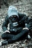 Niño tenso en la careta antigás que se sienta en la tierra Fotografía de archivo libre de regalías
