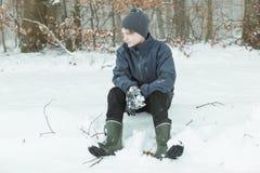 Niño tranquilo que se sienta después de jugar en la nieve Fotos de archivo libres de regalías