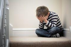 Niño trastornado del problema que se sienta en escalera
